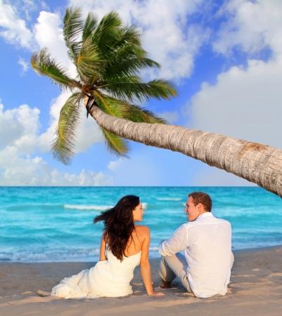 luna de miel: pareja de enamorados sentados en la playa azul en viajes de vacaciones