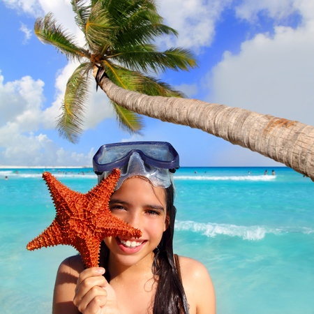 latin tourist girl holding starfish in tropical beach photo