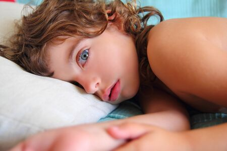 looking at camera: child girl relaxed on pillow looking camera with blue eyes