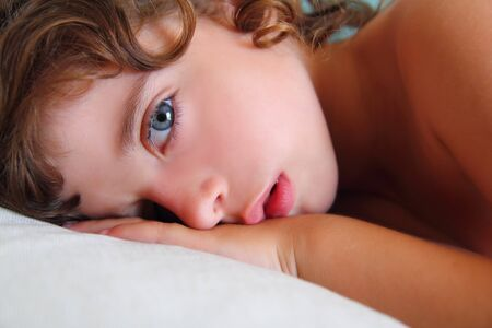 child girl relaxed on pillow looking camera with blue eyes Stock Photo - 11423936