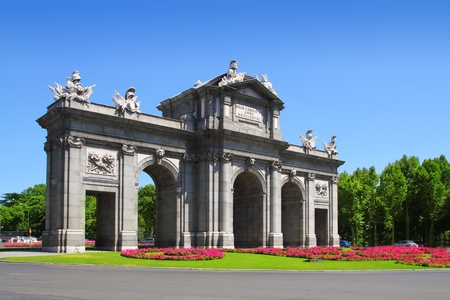 historical landmark: Madrid Puerta de Alcala with flower gardens in Spain