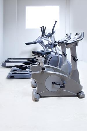 eliptica: amaestrador cruzado el�ptico, bicicleta est�tica y cinta de correr en el gimnasio Foto de archivo