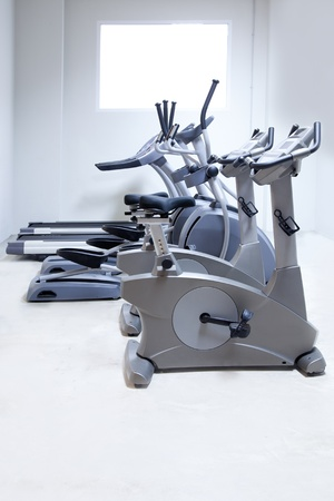 elliptical cross trainer, stationary bicycle and treadmill in gym photo