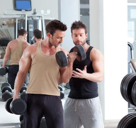 trainer: gym personal trainer man with weight training equipment Stock Photo