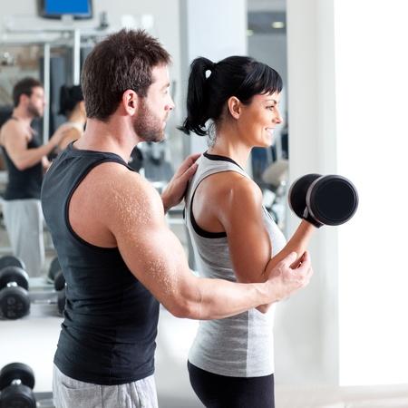 aide à la personne: femme gymnase formateur homme personnel avec du matériel de formation de poids