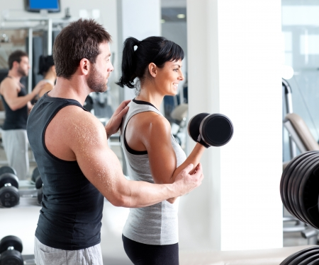 weight weightlifting: gym woman personal trainer man with weight training equipment Stock Photo