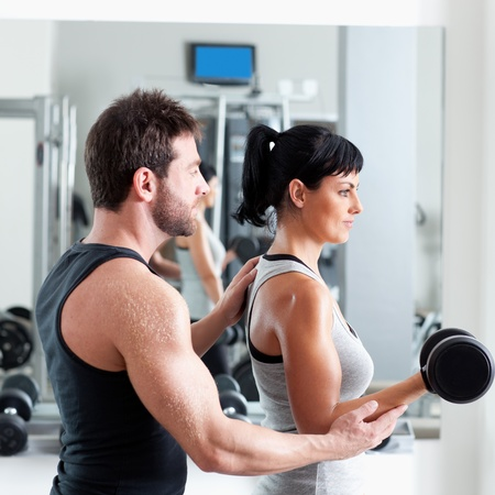 woman lifting weights: gym woman personal trainer man with weight training equipment Stock Photo