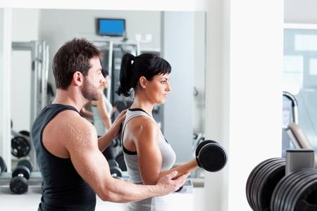 aide � la personne: femme gymnase formateur homme personnel avec du mat�riel de formation de poids