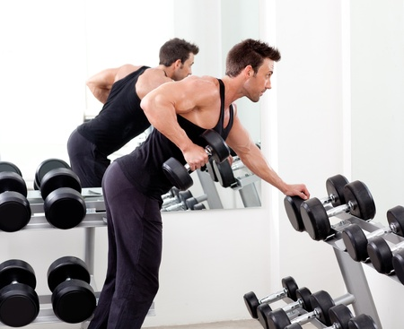 el hombre con el equipo de entrenamiento con pesas en el gimnasio del club deportivo