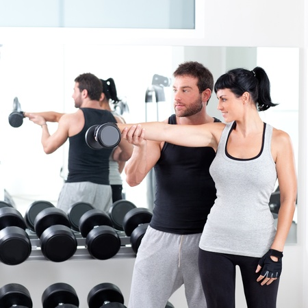 personal trainer: gym woman personal trainer man with weight training equipment Stock Photo