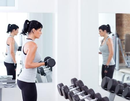 levantar pesas: mujer con equipos de entrenamiento con pesas en el gimnasio del club deportivo Foto de archivo