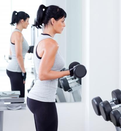 pesas: mujer con equipos de entrenamiento con pesas en el gimnasio del club deportivo Foto de archivo