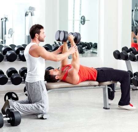 gymnasium: gym personal trainer man with weight training equipment Stock Photo