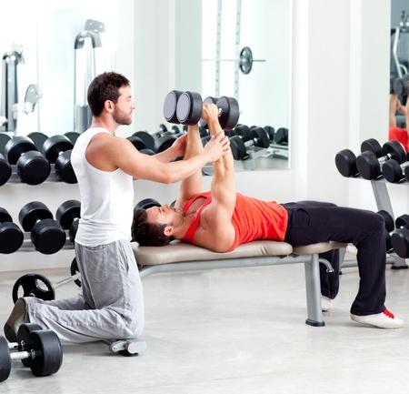 aide à la personne: l'homme formateur salle de gym personnelle avec un équipement de musculation Banque d'images