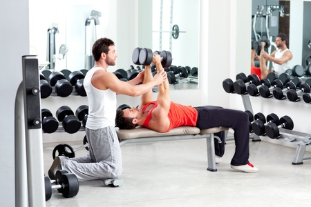 fitness trainer: gym personal trainer man with weight training equipment Stock Photo
