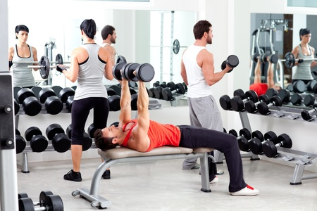 woman lifting weights: group of people in sport fitness gym weight training equipment indoor