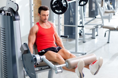 man lifting weights with a leg press on sport gym club photo