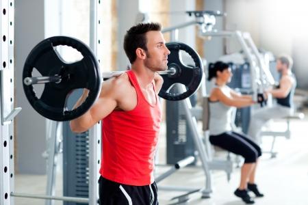 aide à la personne: groupe avec un équipement de formation de poids d'haltère sur gymnase du sport