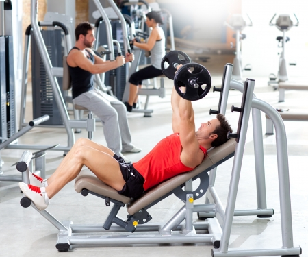 man lifting weights: group with weight training equipment on sport gym club