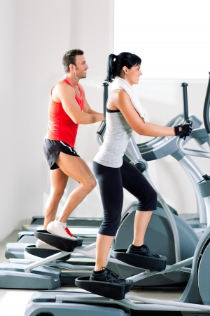 elliptical: man and woman with elliptical cross trainer in sport fitness gym club Stock Photo