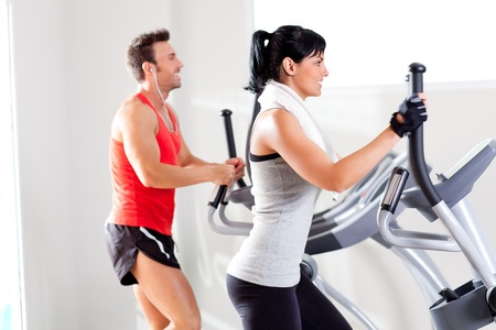 man and woman with elliptical cross trainer in sport fitness gym club photo