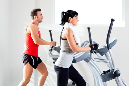 man and woman with elliptical cross trainer in sport fitness gym club Stock Photo - 11982241