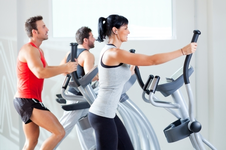 personal trainer woman: man and woman with elliptical cross trainer in sport fitness gym club Stock Photo