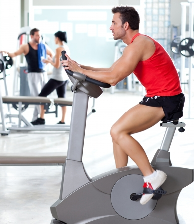man on stationary bicycle at sport fitness gym interior photo