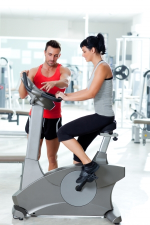 woman on stationary bicycle with personal trainer at  fitness gym photo
