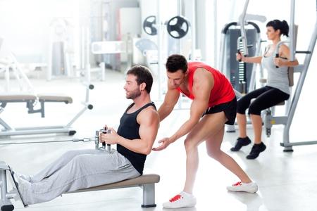 muskeltraining: Mann im Fitnessraum mit Personal Trainer und Fitness-Frau