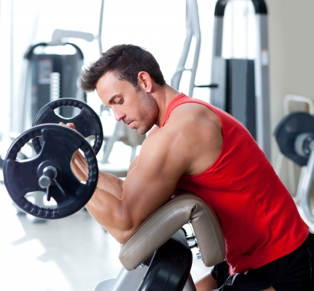 man lifting weights: man with weight training equipment on sport gym club