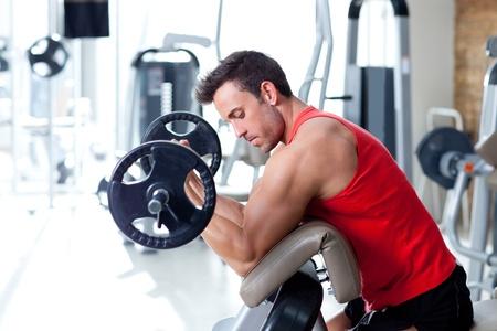 culturista: el hombre con el equipo de entrenamiento con pesas en el gimnasio del club deportivo