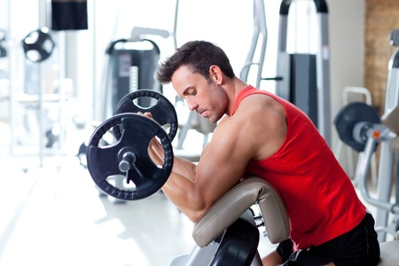 weightlifting equipment: man with weight training equipment on sport gym club