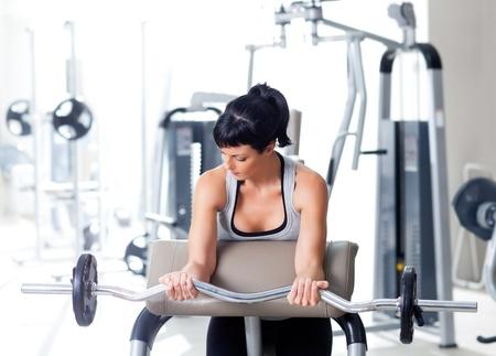 levantar peso: mujer con equipos de entrenamiento con pesas en el gimnasio del club deportivo Foto de archivo