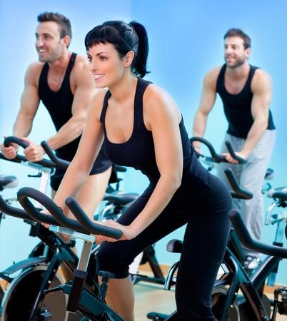 Stationair draaiende fietsen fitness meisje in een sportschool sportclub Stockfoto