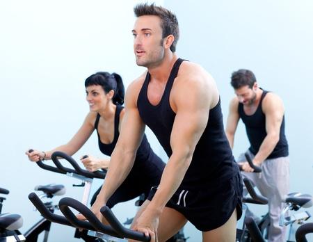 Estacionario bicicleta girando el hombre de fitness en un club deportivo gimnasio