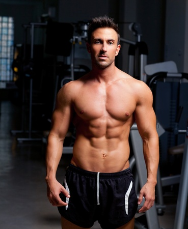 weight weightlifting: fitness shaped muscle man posing on dark gym