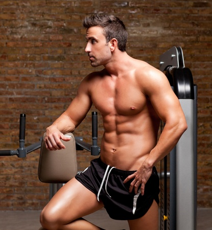 lifting weights: fitness shaped muscle man posing on dark gym