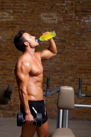 levantar pesas: músculo en forma de hombre en el gimnasio relajante bebida energética potable Foto de archivo