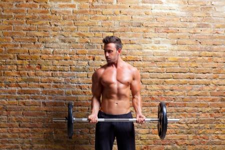 levantando pesas: los músculos del hombre con el cuerpo en forma de pesas en el gimnasio de la pared de ladrillo Foto de archivo