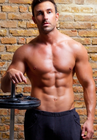 muscle shaped body man with weights on brick wall gym photo