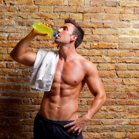 muscle shaped man at gym relaxed drinking energy drink photo