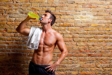 levantar pesas: el hombre músculo en forma en el gimnasio relajada beber bebida energética Foto de archivo
