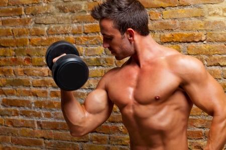 levantar pesas: los músculos del hombre con el cuerpo en forma de pesas en el gimnasio de la pared de ladrillo Foto de archivo
