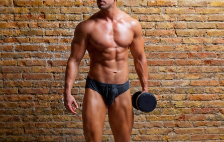 male underwear: muscle shaped underwear man with weight on gym brickwall