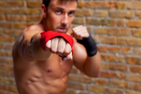 muscle boxer shaped man fist to camera on brickwall photo
