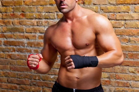 muscle guy: muscle boxer shaped man with fist bandage in red and black on brickwall Stock Photo
