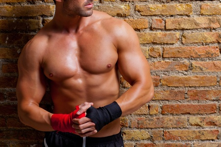 fighters: muscle boxer shaped man with fist bandage in red and black on brickwall Stock Photo