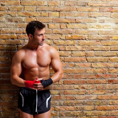 tough: los m�sculos del hombre en forma de boxeador con una venda de pu�o en rojo y negro sobre pared de ladrillo