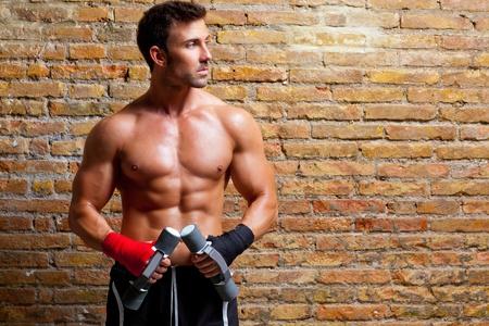 levantar pesas: los músculos del hombre con el vendaje del boxeador puño y cargas de entrenamiento